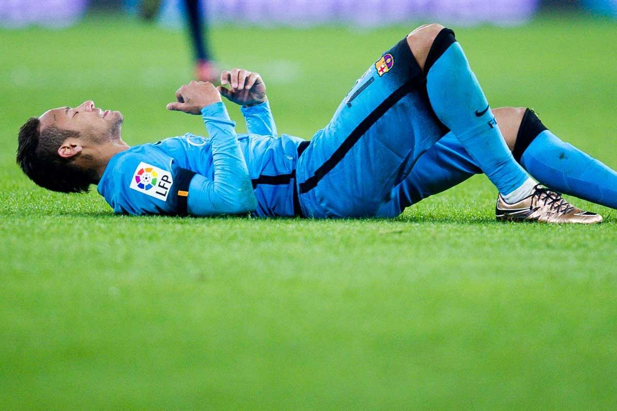Neymar, tirado sobre el césped durante un partido