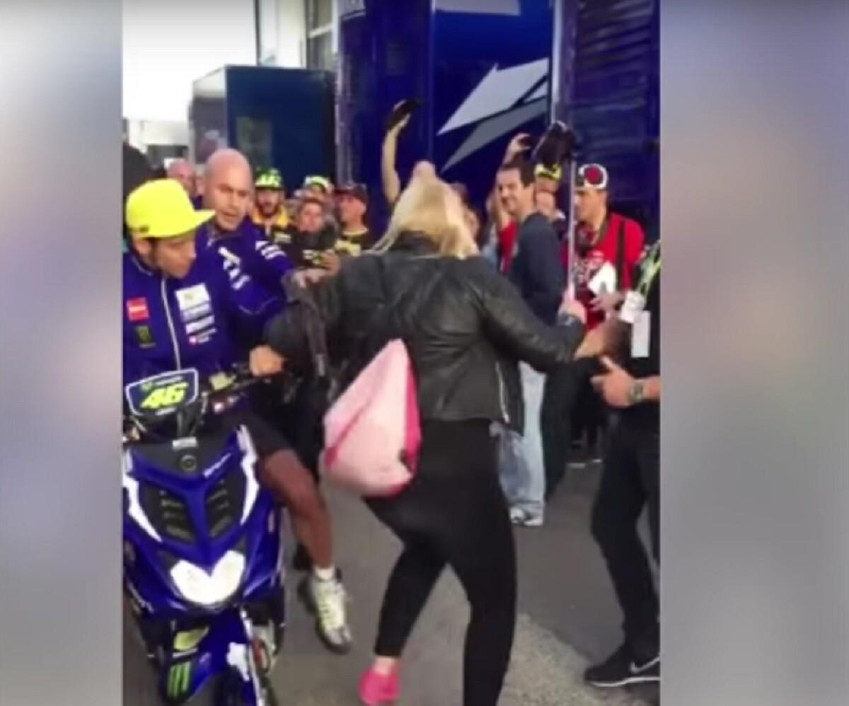 Rossi empuja a una aficionada en el paddock de Valencia